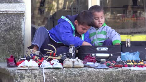 Two-young-boys-sell-shoes-along-a-street-in-Albania