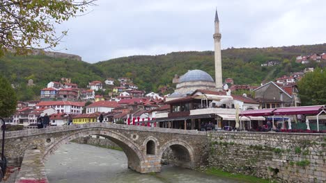 Establishing-shot-of-a-town-in-Kosovo-with-bridge-and-mosque