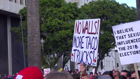 A-huge-protest-against-the-presidency-of-Donald-Trump-in-downtown-Los-Angeles-with-sign-saying-no-walls-more-taco-trucks