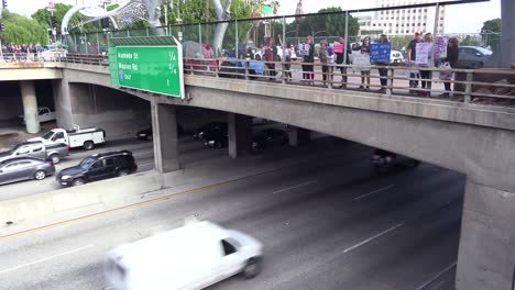 Protestors-against-Donald-Trump-stand-on-an-overpass-in-Los-Angeles-and-passing-drivers-honk-their-support