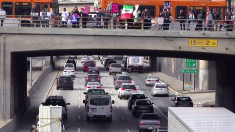 Protestors-against-Donald-Trump-stand-on-an-overpass-in-Los-Angeles-waving-Mexican-flags