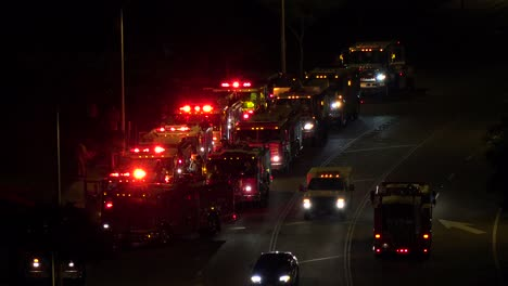 Fire-trucks-and-emergency-vehicles-are-lined-up-in-a-staging-area-at-night-during-an-emergency