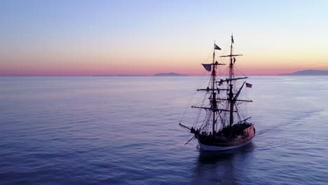 Spectacular-aerial-of-a-tall-sailing-ships-on-the-open-ocean-at-sunset