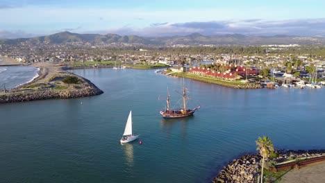 An-aerial-follows-a-tall-ship-entering-Ventura-harbor-California