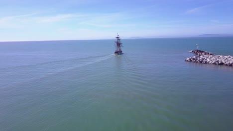 An-aerial-follows-a-tall-ship-leaving-Ventura-harbor-California