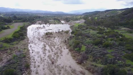 Nice-aerial-shot-flying-over-a-river-flowing-out-of-the-mountains-behind-Ojai-California-1