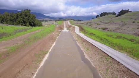 Good-vista-aérea-shot-of-an-aqueduct-flowing-through-the-desert-and-mountains-of-California-3