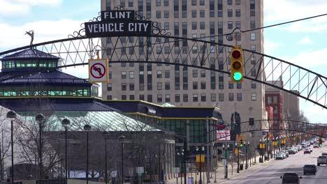Establishing-shot-of-Flint-Michigan-main-street-and-arch-saying-Vehicle-City
