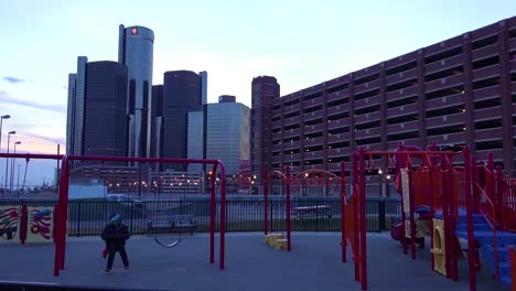 The-GM-tower-at-dusk-along-the-Detroit-River-in-Detroit-Michigan-with-children-playing-foreground
