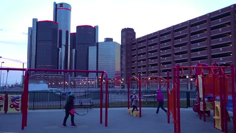 The-GM-tower-at-dusk-along-the-Detroit-River-in-Detroit-Michigan-with-children-playing-foreground-1