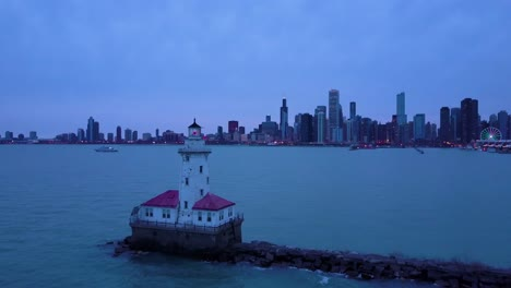 A-beautiful-night-aerial-around-an-iconic-lighthouse-on-Lake-Michigan-with-the-city-of-Chicago-distant-
