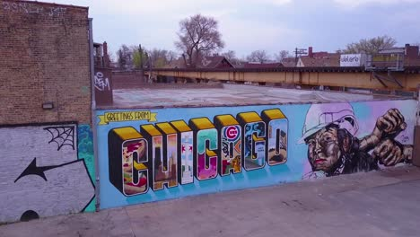 An-aerial-over-a-downtown-Chicago-sign-painted-on-a-wall-as-an-El-train-passes-