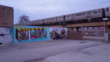 An-rising-aerial-over-a-downtown-Chicago-sign-painted-on-a-wall-as-an-El-train-passes-