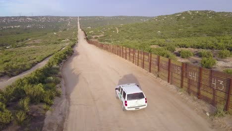 Aerial-over-a-border-patrol-vehicle-standing-guard-near-the-border-wall-at-the-US-Mexico-border