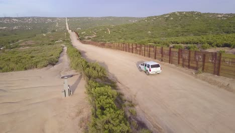 Vista-Aérea-over-a-border-patrol-vehicle-standing-guard-near-the-border-wall-at-the-US-Mexico-border-1