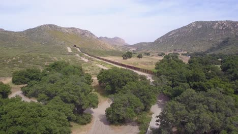 Forward-aerial-shot-of-US-Mexico-border-wall-in-a-rural-area