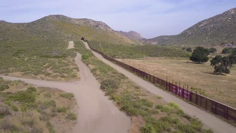 A-low-aerial-along-the-US-Mexican-border-wall-fence-in-a-rural-area-1