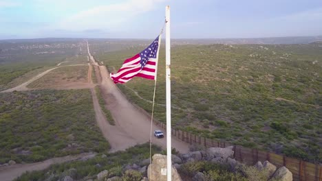 The-American-flag-flies-over-the-US-Mexico-border-wall-in-the-California-desert-as-a-border-patrol-vehicle-passes-below