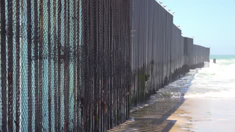 Waves-roll-into-the-beach-at-the-US-Mexico-border-fence-in-the-Pacific-Ocean-between-San-Diego-and-Tijuana