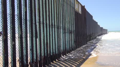 Waves-roll-into-the-beach-at-the-US-Mexico-border-fence-in-the-Pacific-Ocean-between-San-Diego-and-Tijuana-1