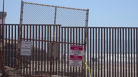 Signs-warn-of-a-restricted-area-at-the-US-Mexico-border-fence-in-the-Pacific-Ocean-between-San-Diego-and-Tijuana