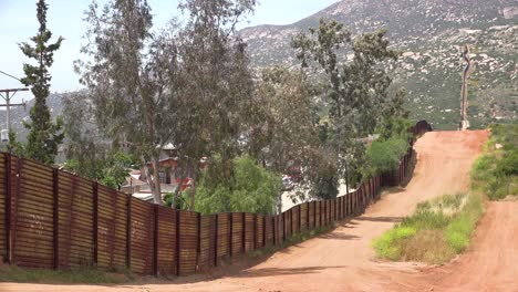 The-US-border-wall-fence-with-the-city-of-Tecate-Mexico-background-2