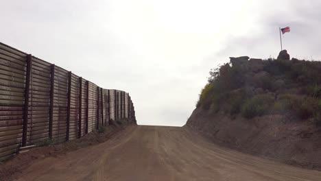 Una-Carretera-Vacía-A-Lo-Largo-De-La-Frontera-Con-México-Con-Una-Bandera-Estadounidense-En-La-Distancia