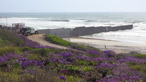 A-Border-Patrol-vehicle-looks-on-as-waves-roll-into-the-beach-at-the-US-Mexico-border-fence-in-the-Pacific-Ocean-between-San-Diego-and-Tijuana