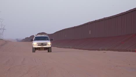 Border-patrol-vehicle-moves-slowly-near-the-border-wall-at-the-US-Mexico-border-at-Imperial-sand-dunes-California-1