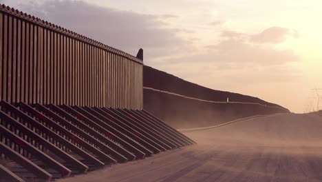 Dust-blows-at-sunset-at-the-border-wall-at-the-US-Mexico-border-near-Imperial-sand-dunes-California