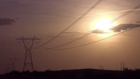 Energy-power-lines-run-across-the-desert-against-the-sun