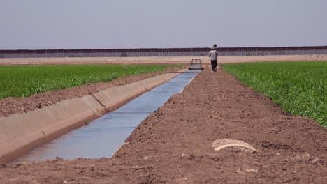 Un-Agricultor-Camina-A-Lo-Largo-De-La-Frontera-Entre-Estados-Unidos-Y-México-Con-El-Muro-Al-Fondo