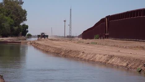 Un-Tractor-De-Agricultores-Sigue-Un-Afluente-Del-Río-Colorado-Que-Fluye-A-Lo-Largo-Del-Muro-Fronterizo-Entre-Estados-Unidos-Y-México