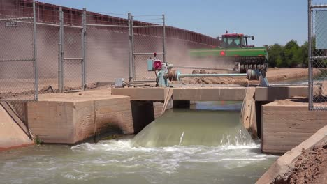 A-farmers-tractor-follows-a-tributary-of-the-Colorado-River-as-it-flows-along-the-border-wall-between-the-US-and-Mexico-1