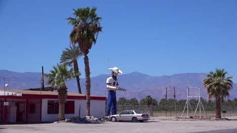 A-large-statue-of-a-cowboy-stands-outside-a-desert-bar-or-saloon-1