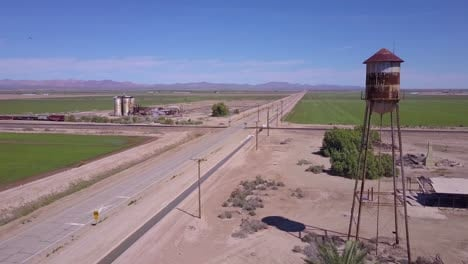 A-high-angle-aerial-over-a-lonely-abandoned-road-through-a-rural-area-with-water-tower-foreground