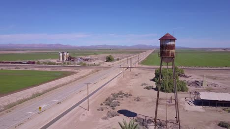 A-high-angle-aerial-over-a-lonely-abandoned-road-through-a-rural-area-past-water-tower-foreground