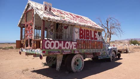 A-truck-painted-with-Bible-verses-and-promoting-Jesus-sits-at-a-Christian-hippy-commune-at-Slab-City-California