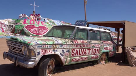 A-car-painted-with-Bible-verses-and-promoting-Jesus-sits-at-a-Christian-hippy-commune-at-Slab-City-California