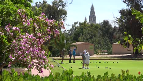 Seniors-engage-in-lawn-bowling-in-San-Diego-with-old-Spanish-colonial-buildings-background
