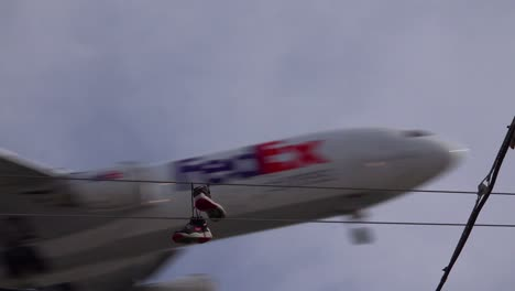A-nice-low-angle-of-tennis-shoes-on-a-line-as-a-FedEx-plane-lands-in-Southern-California