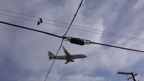 A-nice-low-angle-of-tennis-shoes-on-a-line-as-a-FedEx-plane-lands-in-Southern-California-1