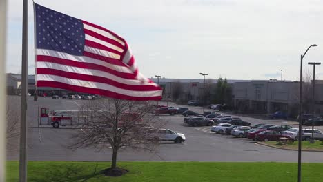 An-establishing-shot-of-a-shopping-mall-with-American-flag-flying-foreground