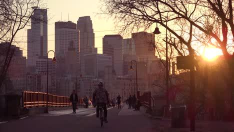 Hermosa-Foto-De-Peatones-Caminando-Al-Atardecer-Con-El-Fondo-Del-Horizonte-De-Minneapolis-Minnesota
