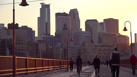 Hermosa-Foto-De-Peatones-Caminando-Al-Atardecer-Con-El-Fondo-Del-Horizonte-De-Minneapolis-Minnesota-1
