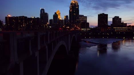 Una-Foto-Nocturna-Del-Centro-De-Minneapolis,-Minnesota,-Con-El-Río-Mississippi-En-Primer-Plano