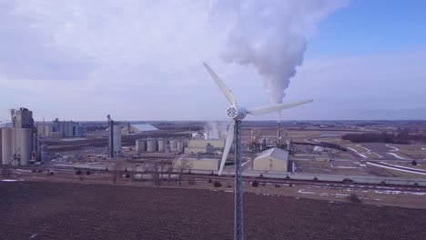 An-aerial-shot-over-an-oil-refinery-with-a-windmill-foreground-contrasting-energy-sources