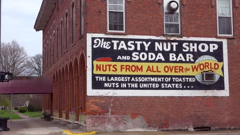 Establishing-shot-of-a-sign-on-a-brick-building-saying-nut-shop-and-soda-bar-