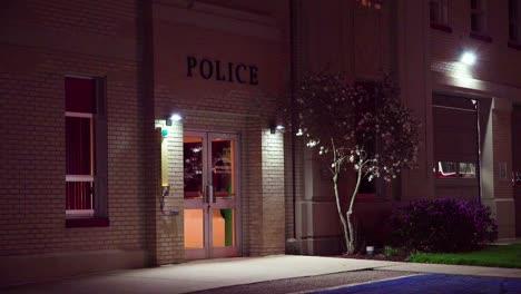 Exterior-establishing-shot-of-a-small-police-station-at-night