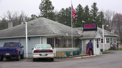 Establishing-shot-of-a-small-generic-roadside-diner-restaurant-with-a-neon-sign-saying-EAT